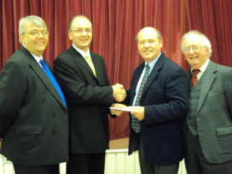 Pictured from left to right: Paul Bennett - Choir Treasurer:  Mark Ritzmann – Choir Chairman and Music Director: Tom Defis – Christian Aid Area Coordinator: Reverend Patrick Baker – President of Neath Council of Churches